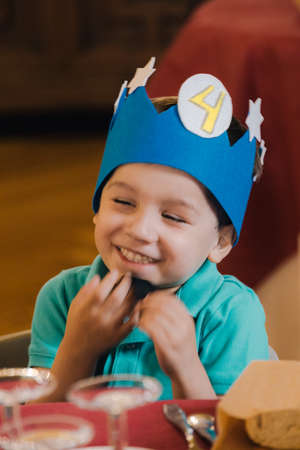 portrait of a smiling Caucasian boy sitting with a cardboard crown celebrating his fourth birthday with selective focus