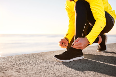 Running shoes being tied by man getting ready for jogging. Closeup. Shallow depth of field, focus on hands.