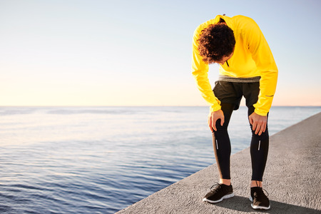 Workout outdoor runner. Man running taking a break from run outside in beautiful seaside. Fit young caucausian athletic model training for marathon outdoors