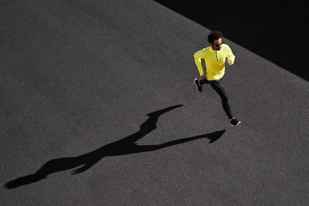 Running man sprinten voor succes op de run. Bovenaanzicht atleet runner training op hoge snelheid op zwart asfalt. Gespierd fit sportmodel sprinter oefenen sprint in het geel sportkleding. Kaukasische fitness model in zijn jaren '20.