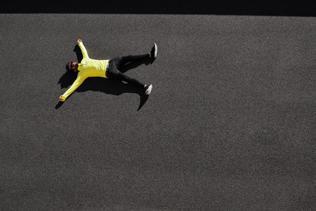 Top view runner in yellow sportswear resting lying on a black asphalt after running. Jogging man taking a break during training outdoors. Caucasian fitness model 20s in Barcelona, Spain. Stock Photo