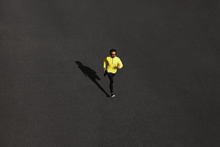 Top view runner man running sprinting for success on run at black road in yellow sportswear. Muscular fit sport model sprinter exercising sprint on city road. Full body length of Caucasian model. Imagens