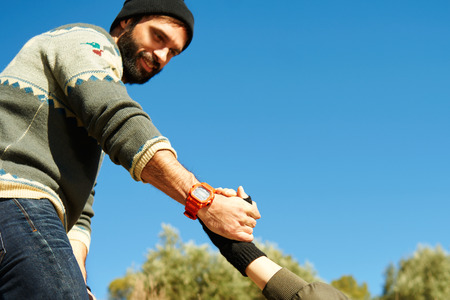 Helping hand - hiking girl get help from a smiling man focus at hands on hike happy overcoming obstacle. Active lifestyle hiker couple traveling. Beautiful mixed race Asian Caucasian female model. Stock Photo