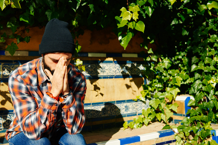 indecisive: Confused man - people feeling confusion and chaos. Indecisive, disorientated and bewildered man stressed with headache over decision making. Boy in 20s on green plants background. Asian  Caucasian.