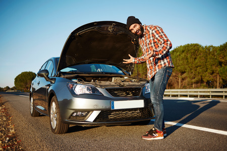 Car owner - young man puzzled breaking car and male surprised about this tragedy. Sad model standing beside broken car and threw up his hands. Beautiful young mixed race Caucasian brutal man. Stock Photo
