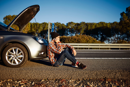 Young brutal man sits near car talking on cell phone because his auto broken down. Thoughtful 20s mixed race Caucasian Asian male on a beautiful bright sunny summer day trying to call friend that they help repair car.