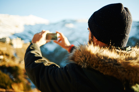 Happy man taking selfie self-portrait photo hiking. Hikers holding camera and take a shot of himself outdoors at sunset on a background of snow mountains of Granada, Spain. photo
