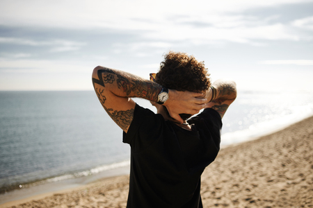 Close up back portrait man on beach standing in sand with hands behind head and looking into the distance enjoying sun and summer travel holidays vacation getaway in Barcelona. Beautiful young multiracial Caucasian man with tattoos.
