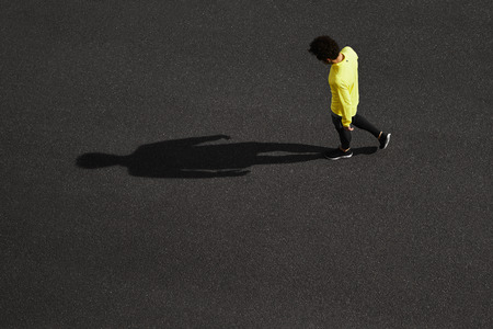 Unrecognizable runner standing at side position. Top view jogging man taking a break during training outdoors in on black asphalt on top view. Caucasian male runner and fitness sport model after work out.