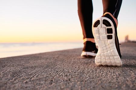 Runner Mann Fuß auf der Straße Nahaufnahme auf Schuh laufen. Männliche Eignung Athlet Jogger Training im Wellness-Konzept bei Sonnenaufgang. Sport gesunden Lifestyle-Konzept.