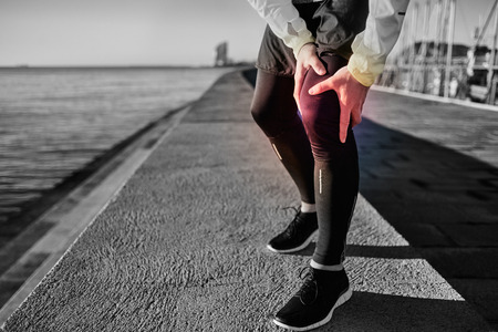 atleta: Knee Injury - sports running knee injuries on man. Close up of legs, muscle and knee outdoors. Male fitness athlete runner with pain from sprain knee.