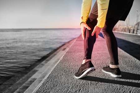 leg calf injury: Muscle injury - Athlete running clutching calf muscle after spraining it while out jogging on the beach near ocean. Sports injury concept with running man outside.
