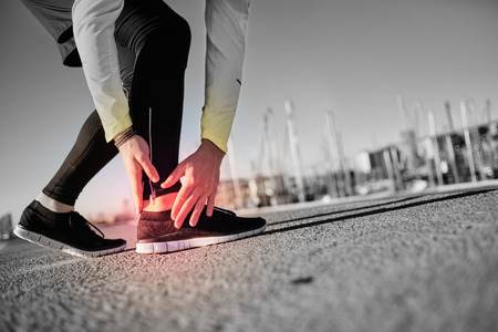 adult foot: Broken twisted ankle - running sport injury. Athletic man runner touching foot in pain due to sprained ankle.