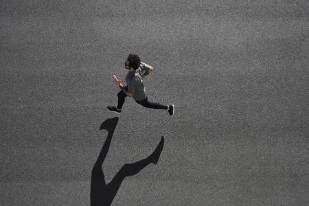 coureur: Haut de la formation coureur vue de l'athlète, sur la route noire dans le sportswear noir à la position centrale. Musclé ajustement modèle sportif sprinter exercice sprint sur la route de la ville. La pleine longueur de corps de modèle de race blanche.