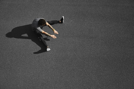 Unrecognizable runner sitting at side position. Top view jogging man taking a break during training outdoors in on black asphalt on top view. Caucasian male runner and fitness sport model after work out. 版權商用圖片
