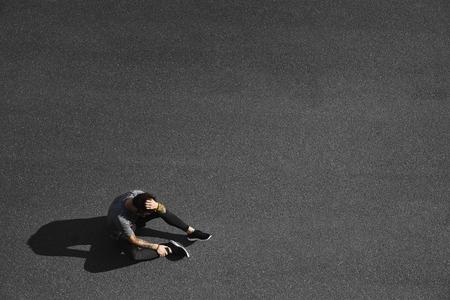 hombre deportista: Gimnasio Sport hombre que se relaja después del entrenamiento. Joven atleta masculino que descansa sentado en el asfalto después de correr y ejercicio de entrenamiento al aire libre en verano. Caucásica modelo de hombre deportivo.