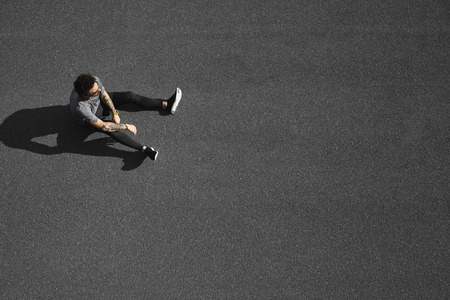 Runner resting tired and exhausted after running. Jogging man taking a break during training outdoors in road. Young Caucasian male fitness model after work out. Imagens