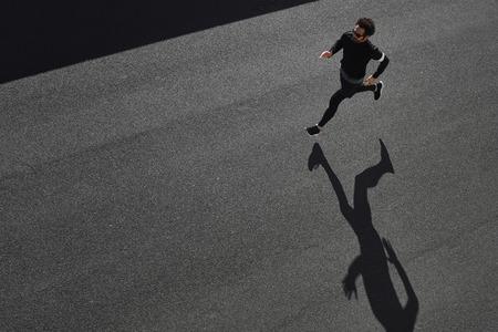 Bovenaanzicht atleet runner training op weg in zwarte sportkleding bij de centrale positie. Gespierd fit sport model sprinter oefenen sprint op de stad weg. Full body lengte van Kaukasische model.