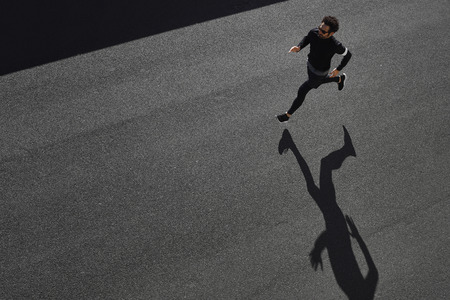 Top view athlete runner training at road in black sportswear at central position. Muscular fit sport model sprinter exercising sprint on city road. Full body length of Caucasian model.