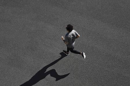 Bovenaanzicht atleet runner training op zwarte weg in sportkleding bij de centrale positie. Gespierd fit sportmodel sprinter uitoefenen sprint op de stad weg. Full body lengte van Kaukasische model.