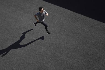 coureur: Haut de la formation coureur vue de l'athlète, sur la route dans le sportswear noir à la position centrale. Musclé ajustement modèle sportif sprinter exercice sprint sur la route de la ville. La pleine longueur de corps de modèle de race blanche.