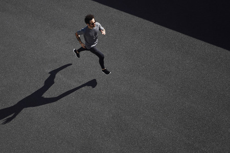 the athlete: Top view athlete runner training at road in black sportswear at central position. Muscular fit sport model sprinter exercising sprint on city road. Full body length of Caucasian model.