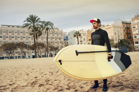 neoprene: Young attractive surfer sports man wearing a neoprene diving suit and looking at the horizon while carrying his surfing board during a cloudy day