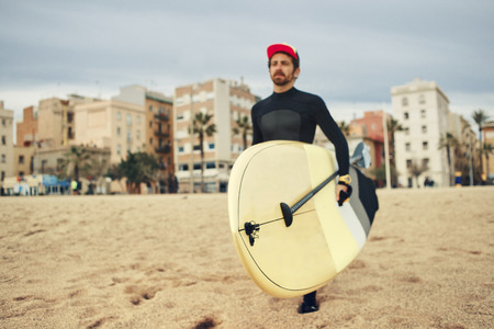 neoprene: Young surfer sports man wearing surfing neoprene waterproof suits and carrying his surfing board on a white sand beach