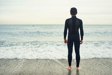 neoprene: Surfer sports man wearing surfing neoprene waterproof suits on a sand beach with a blue sky Stock Photo