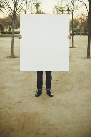 거리에 흰색 빈 포스터를 들고 남자
