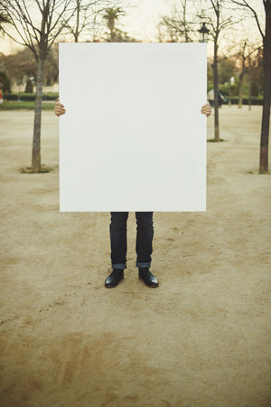 Man holding white blank poster on a street Imagens