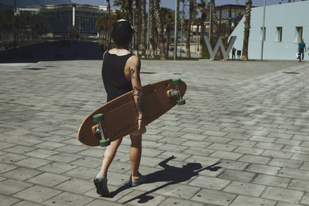 goes: Young man goes through the city on a sunny day near the business center and keeps his longboard