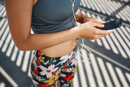 Unrecognizable close up portrait of young fitness blonde woman in sportswear listening music with headphones after training outdoors at beautiful sunny day.