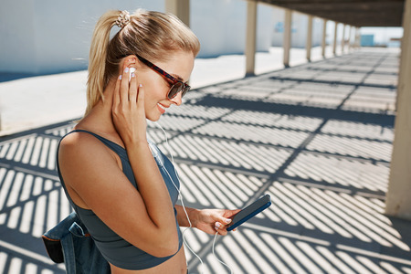 smart girl: Young fitness blonde woman in sportswear listening music with headphones after training outdoors at beautiful sunny day. Girl runner enjoying the sun and listen music in earphones from smart phone mp3 player smartphone. Stock Photo