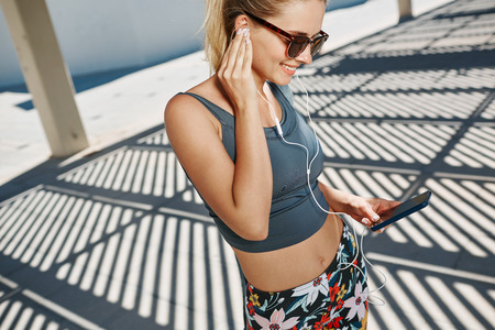 Close up portrait of young fitness blonde woman in sportswear listening music with headphones after training outdoors at beautiful sunny day.
