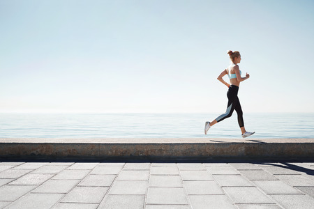 Running Aziatische vrouw. Vrouwelijke agent opleiding buiten de kust atleet op prachtige zonsondergang of 's morgens op het strand.