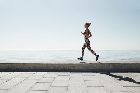 Jogging athlete young woman running at sea background. Fitness runner training outside by the ocean sea in beautiful sunset or sunrise in sports clothing in summertime.