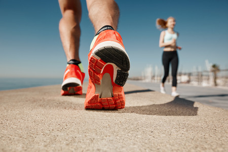 corriendo: Pies del corredor que se ejecutan en primer plano de carreteras en el zapato. Deportista concepto de fitness trotar amanecer entrenamiento wellness.
