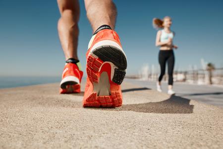exercise man: Runner feet running on road closeup on shoe. Sportsman fitness sunrise jog workout welness concept.