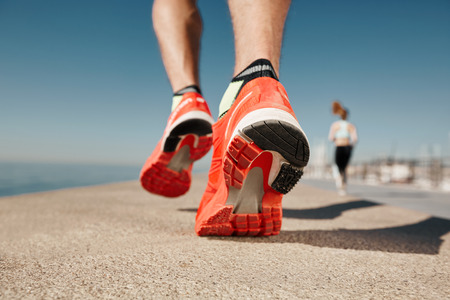 Close up runner feet. Man runner legs and shoes in action on road outdoors at road near sea. Male athlete model. Banco de Imagens - 41302639