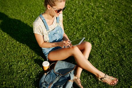 Young blonde girl using tablet outdoor sitting on grass and smiling. Student using digital tablet after school at park. photo