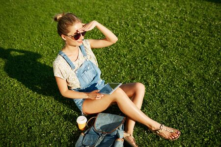 Young happy blond girl looking into the distance with coffee and pc tablet outdoor sitting on grass and smiling. photo