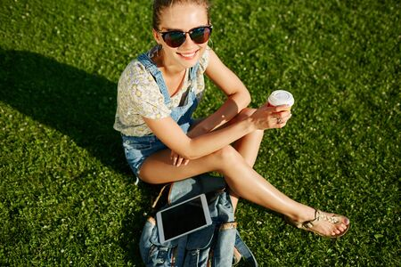 Close up portrait of young blonde girl with coffee and tablet outdoor sitting on grass and smiling. photo