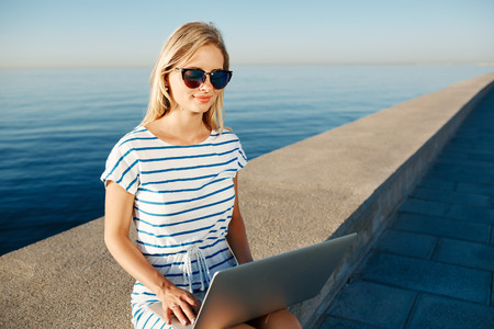 communicates: Beautiful young woman sitting on beach with laptop smiling and communicates over the Internet via Wi Fi