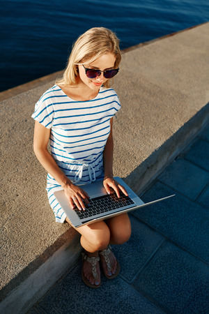 communicates: Beautiful young female blonde sitting on beach with laptop smiling and communicates over the Internet via Wi Fi