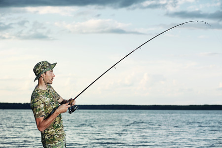 freshwater sailor: Man fishing on the lake during his vacation Stock Photo