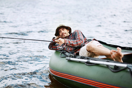 young happy boy on vacation lying in the boat smile and fishing