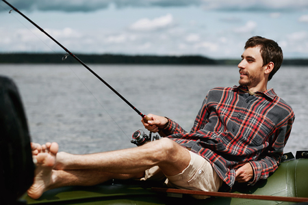 freshwater sailor: young happy man on vacation lying in the boat smile and fishing