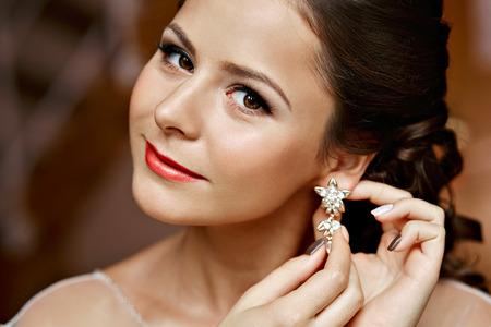 Donna che mette sul orecchini di diamanti. Bellezza signora caucasica cercando e gioielli commerciale.