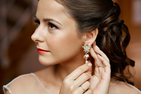 the caucasian beauty: Woman putting on diamond earrings. Caucasian beauty lady trying and shopping jewelry.